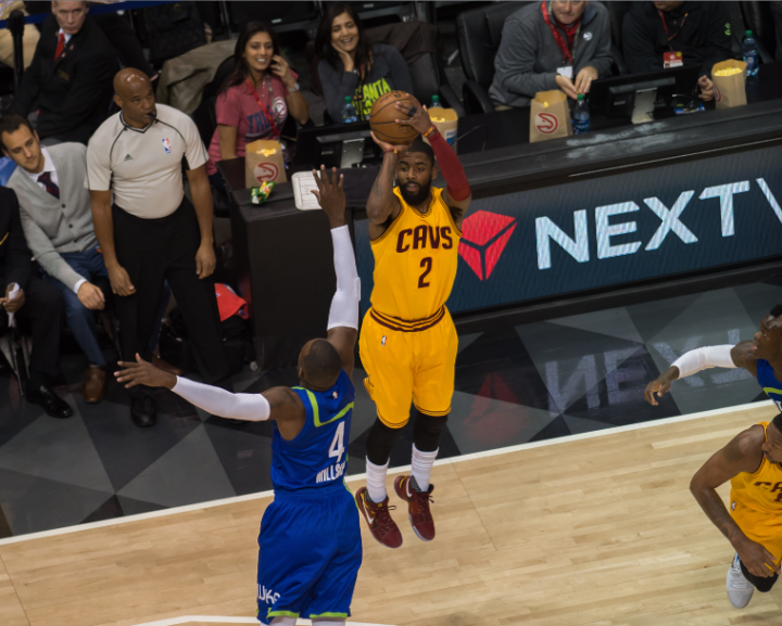 Cleveland's Kyrie Irving goes deep for three over Atlanta's Paul Millsap (Hakim Wright)